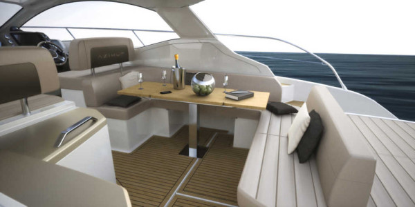 The exterior living area of Azimut Atlantis 43 is furnished with a dining room table, a sofa, and a kitchen area