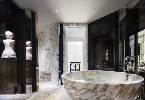 The Master Bathroom of the suite is furnished with a large, free-standing, circular bathtub with a built-in TV, waterfall feature, his and her vanities and underfloor heating